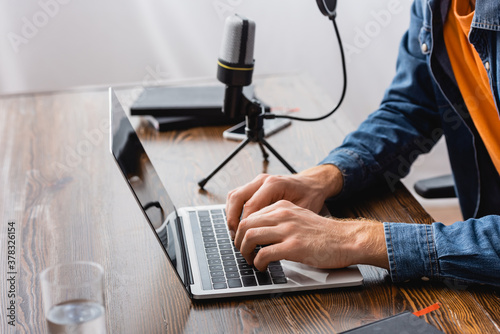 cropped view of broadcaster typing on laptop near microphone at workplace Fototapeta