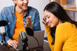 excited asian woman covering face with hand near interviewer in radio studio