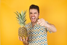 Portrait Of Strong And Determined Young Man Holding Pineapple Wearing Hawaiian Shirt Over Yellow  Punching Air With Fist And Looking Confidently At Camera, Male Struggle, Fighting Spirit.