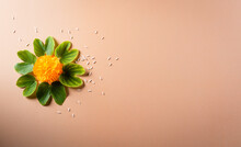 Happy Dussehra. Yellow Flowers, Green Leaf And Rice On Orange Pastel Background. Dussehra Indian Festival Concept.