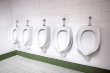 Row Of White Urinals In A Publ...
