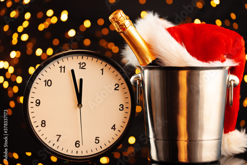 Fototapeta New Year eve concept with alarm clock against blurred garland