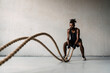 Image of african american sportsman working out with battle ropes