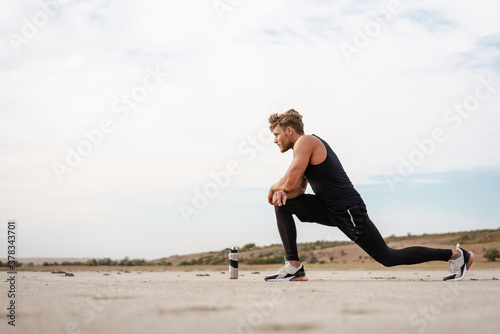 Photo of athletic young sportsman doing exercise while working out Canvas