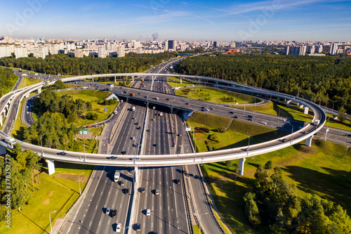 Fototapeta a panoramic view of the road with a complex system of interchanges with the city in the background filmed from a drone obraz