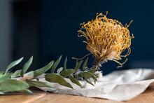 Dried Bright Yellow Protea On A Craft Brown Sheet Of Paper On A Table