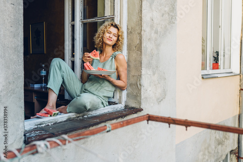 Valokuva Funny blond curly woman get ready with appetite bites of watermelon sitting on windowsill