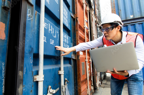 Import and export concept. Fore man shipper using tablet and computer laptop to monitor container and seal number status at container yard. Foreman control loading Containers box