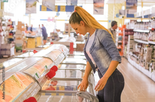 Woman choosing frozen dairy products at supermarket Canvas Print