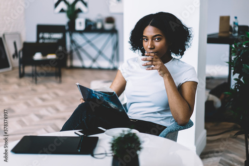 Fotografering Emotionless young woman reading magazine on sofa and drinking coffee