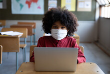 Portrait Of Black African American Boy Wearing Face Mask Using Laptop On His Desk At School