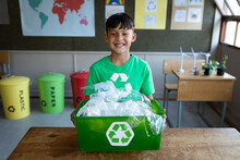 Portrait Of Boy Holding A Recycle Container In Class At School