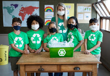 Portrait Of Female Teacher And Group Of Kids Wearing Face Masks With Recycle Container At School