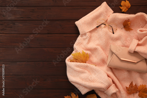 Fotografia, Obraz Warm sweater, bag and dry leaves on brown wooden background, flat lay with space for text