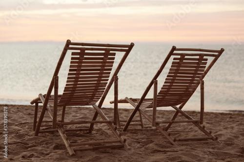 Obraz Wooden deck chairs on sandy beach at sunset. Summer vacation - fototapety do salonu