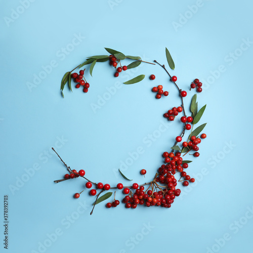 Fototapeta Red berries and leaves arranged in shape of wreath on light blue background, flat lay with space for text. Autumnal aesthetic obraz