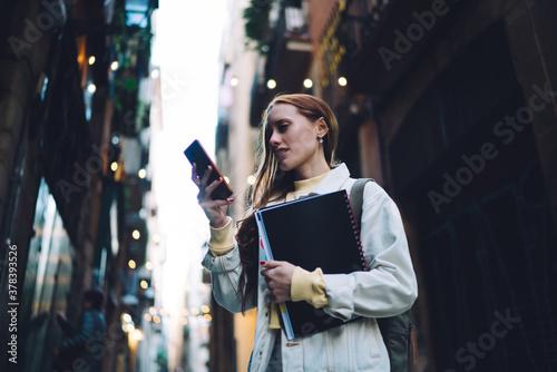 Confident modern female student texting on street Tapéta, Fotótapéta