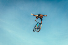 Young Man Performing Stunt With Bicycle Against Blue Sky At Park During Sunset