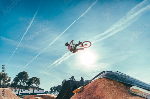 Carefree young man performing stunt with bicycle against blue sky at park during sunset