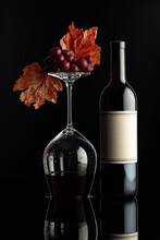 Bottle Of Red Wine And An Inverted Glass With Wine On A Black Background.