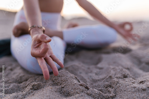 Close-up of young woman meditating on sand at beach