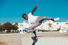 Young Man Jumping Over Retaining Wall Against Clear Blue Sky During Sunny Day