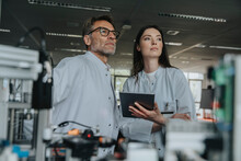Thoughtful Male And Female Engineers Looking Away While Standing By Machinery In Laboratory