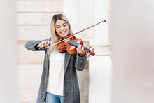 Blond Young Woman Playing Violin In City
