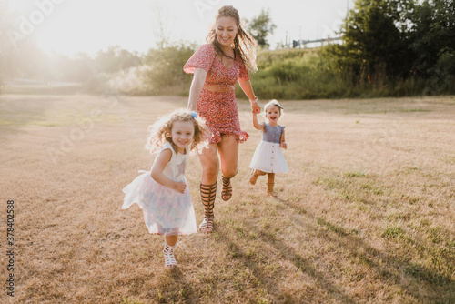 Happy mother running with daughters on a meadow in backlight - 378402588
