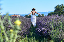 Woman Wearing White Dress And Hat Walking Amidst Lavender Field Against Clear Sky