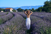Woman Wearing White Dress And Hat Standing Amidst Lavender Field