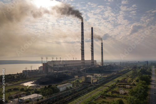 Fototapeta Aerial view of high chimney pipes with grey smoke from coal power plant. Production of electricity with fossil fuel. obraz