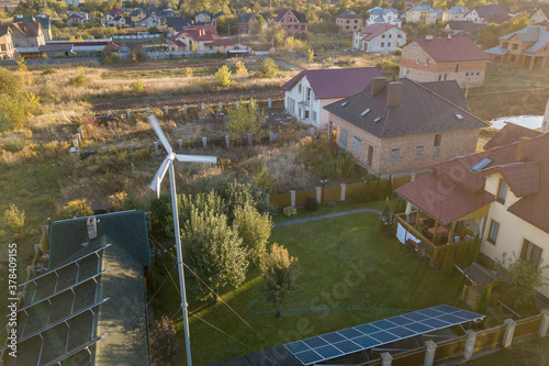 Fototapeta Aerial view of a residential private house with solar panels on roof and wind generator turbine. obraz