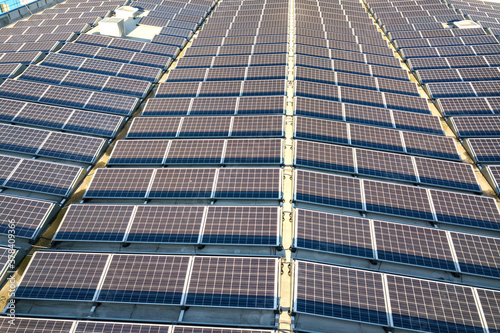 Fototapeta Aerial view of many photo voltaic solar panels mounted of industrial building roof. obraz