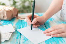 A Woman Writes On An Empty Postcard. Hands Holding A Pen Close-up. Blue Wooden Table With A Parcel In The Background. The Concept Of Mail Correspondence And Postcrossing