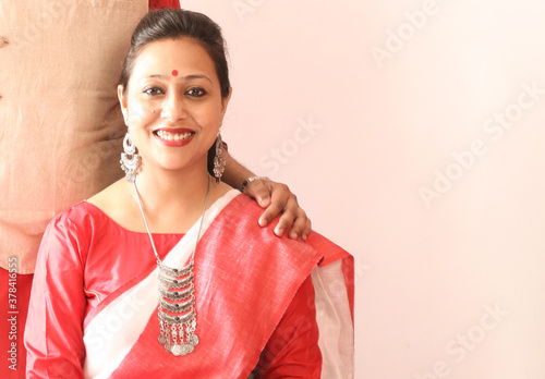 Valokuva a young indian bengali assamese married lady dressed in red and white saree and