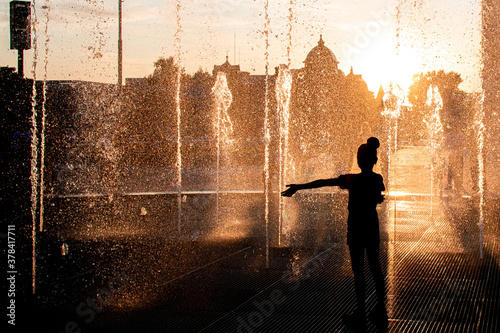 Silhouette of a girl at the fountain in the sunset light Canvas