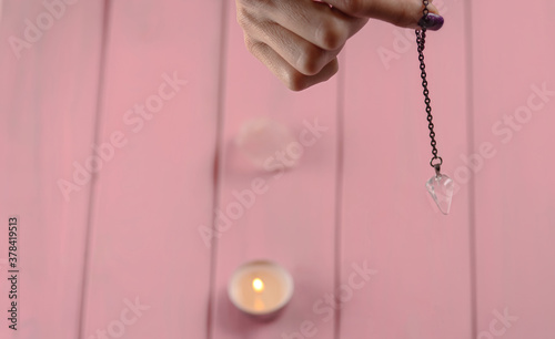 Fotomural Arm of a dowser with hand-held pendulum on a chain with a natural crystal on a background of pink wood texture with burning candles