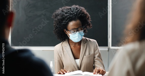 Fototapeta Young African American female teacher in glasses and medical mask sitting at table in school at class, reading textbook and teaching
