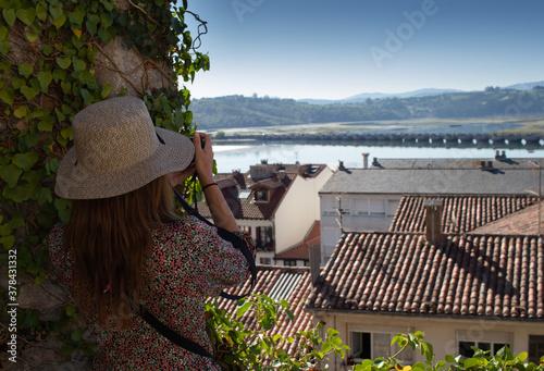 Obraz na plátne Mujer fotografiando el paisaje de la ciudad de San Vicente de la Barquera, en España