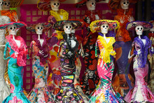 Small Dolls For Dia De Los Muertos, Which Means Day Of The Dead In English. The Dolls Are On Display At A Market, And Are Bright And Colourful.