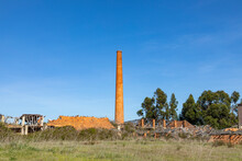 Old Rotten Factory With Damaged Roof And Old Brick Chimney In Sines, Region Setubal As Symbol For Former Industry