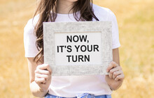 Now It's Your Turn To Write Text, An Inscription, A Phrase In A Frame That The Girl Is Holding In Her Hands. Business Concept.
