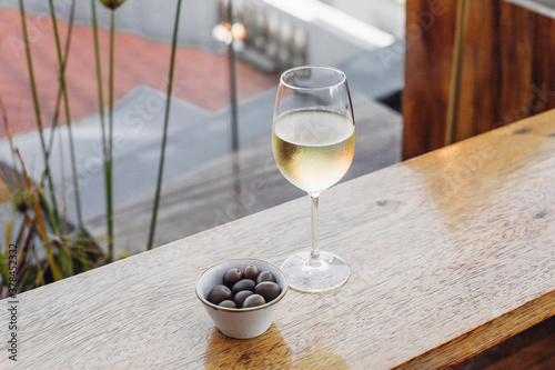 A glass of wine with olives in a bar, rooftop view Canvas