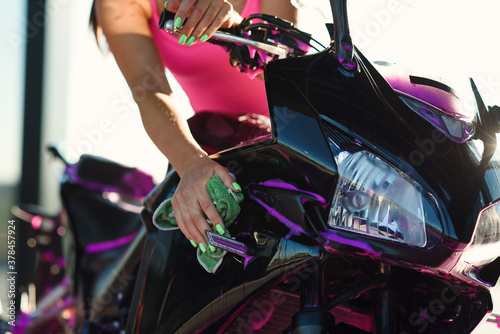 Beautiful girl in pink t-shirt washes stylish sport motorcycle and wipes it from magenta foam at self-service car wash.