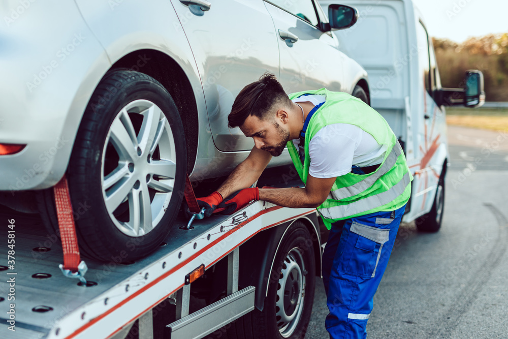 Fototapeta Handsome middle age man working in towing service on the road. Roadside assistance concept.