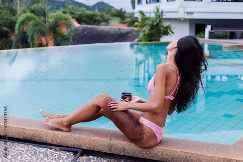 Fototapeta Outdoor portrait of woman in pink bikini at spa by swimming pool holding coffee scrab applies on slim body.   obraz na płótnie