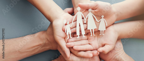 Leinwand Poster Adult and children hands holding paper family cutout, family home, foster care,