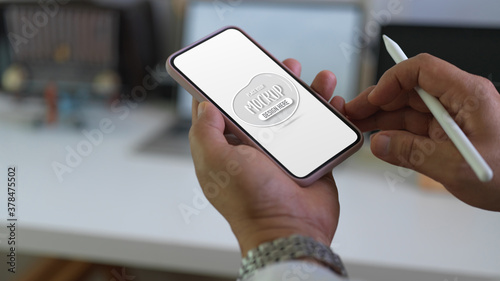 Photo Male using mock up smartphone while holding stylus in blurred worktable backgrou
