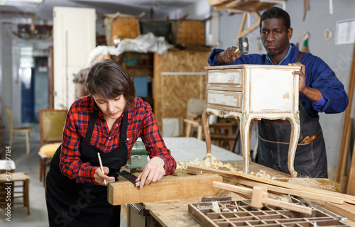 Foto Portrait of male and female artisans in process of renewing vintage chest of dra